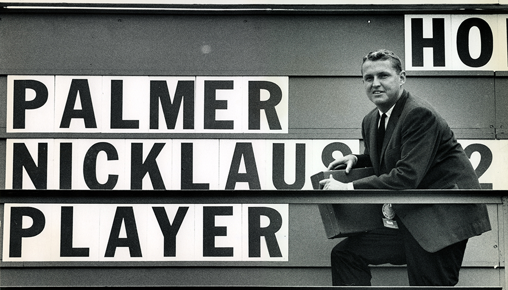 Mark McCormack standing by golf scoreboard reading the names, Palmer, Nicklaus, Player.