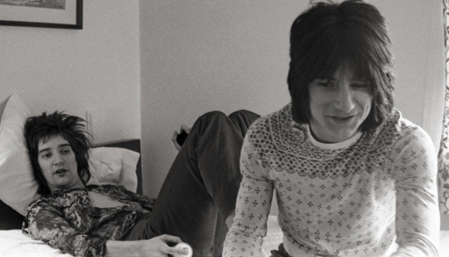 Rod Stewart, lying in a bed and Ron Wood sitting on the edge of the bed in a hotel room.