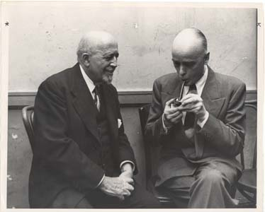 W. E. B. Du Bois seated with unidentified man smoking a pipe, circa 1958