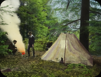 Two Young Men camping in the woods - cooking food over fire next to tent