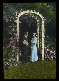 Couple under flower- covered white garden arch