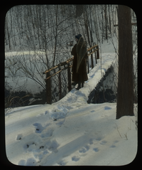 Winter in the Glen, MAC (Person on footbridge carrying snowshoes in snow)