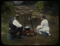 Man and Woman cooking at campfire