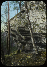 Hiker beneath rock cliff in woods