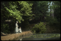 George W. Cable Garden (two women looking into pond with water lilies, trees in background)