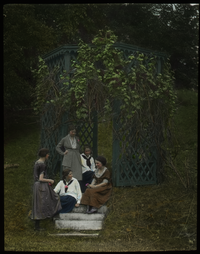 Young women sitting on steps by grape arbor