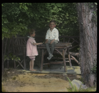 Mr. Muller's Garden (Children sitting on rustic garden furniture)