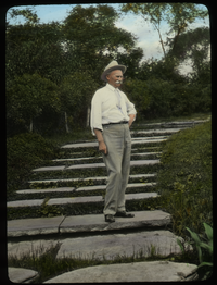 Jens Jensen (man standing on wide steps with plants around)