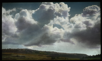 Large clouds over grassy landscape