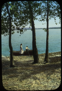 Boy and girl with rowboat at water's edge