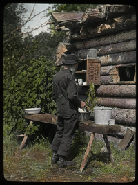Washing dishes in camp P.Q.(elderly man outside log camp)