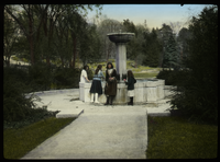 Girls by a fountain in a formal garden/ park