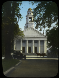 White classical style building (church or meeting house) along street with auto and horse