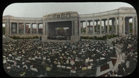 Large crowd seated around stage in an outdoor theater