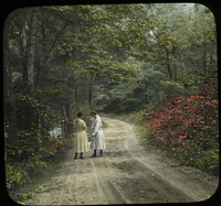 Two women on dirt road bordered by trees and shrubs