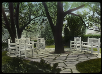 Tree surrounded by flag stone patio with white wooden chairs and benches (damaged slide)