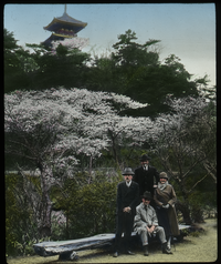 Japan (westerners in front of flowering tree, shrine in background)
