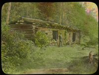 Log camp, Lake Vassal P.Q. (man outside log cabin besides forest)