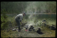 Lake Vassal, Quebec (man tending campfire by lake)