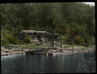 Camp- Lake Vassal P.Q. (log cabin and raft by a lake)