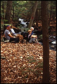 Dan and Nina Keller, dogs, mother(?) resting on walk in woods, Wendell