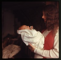 Nina standing, holding baby (Eben)
