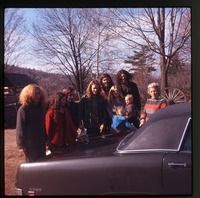 Chuck, Nina, four men, Janis, two babies, Nina's mother, standing by car
