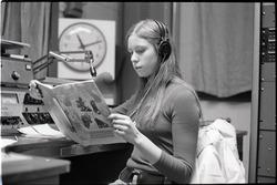 Unidentified woman reading Free Spirit Press magazine in radio studio