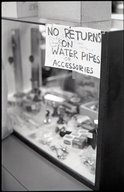 "Head shop with sign at counter reading ""No return on water pipes or accessories"" (close-up of sign), linking to the digital object"
