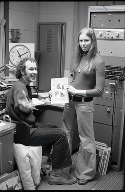 Richard Safft and unidentified woman with copy of Free Spirit Press magazine in radio broadcast studio