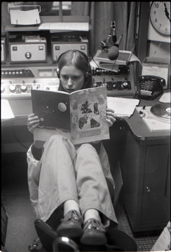 Unidentified woman reading Free Spirit Press magazine in radio studio