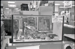"Head shop with sign at counter reading ""No return on water pipes or accessories"" (close-up of counter)"