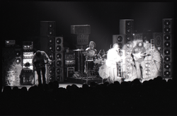 Grateful Dead concert at Springfield Civic Center: band in performance in front of a wall of speakers (spotlight on Bob Weir and Jerry Garcia) (Springfield, Mass.), linking to the digital object