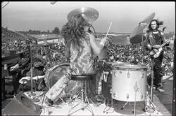Hollywood Speedway Rock Festival: Jo Jo Gunne in performance, view from behind drummer (Curly Smith), bassist (Jimmy Randall) looking on (Pembroke Pines, Fla.), linking to the digital object