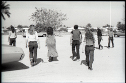 Hollywood Speedway Rock Festival: group of young people (commune members?) walking away from the camera (Pembroke Pines, Fla.), linking to the digital object