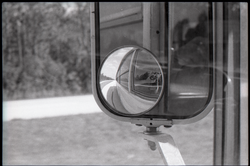 Side mirror on bus, with image of camera man reflected (Pembroke Pines, Fla.), linking to the digital object