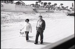 Middle-aged couple walking on beach with pet dog (Pembroke Pines, Fla.), linking to the digital object