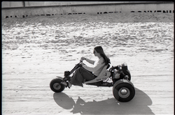 Young woman riding motorized trike on beach (Pembroke Pines, Fla.), linking to the digital object