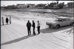 Three women and three men, all middle-aged, walking along the beach, beach homes in background (Pembroke Pines, Fla.), linking to the digital object