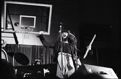 Jethro Tull in concert at the Springfield Civic Center: Ian Anderson at microphone with flute (basketball hoop in background) (Springfield, Mass.), linking to the digital object