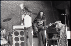 Rapunzel in concert: blurred image of Michael Metelica (vocals), John Sullivan (bass), Mark Holland (keyboards), linking to the digital object