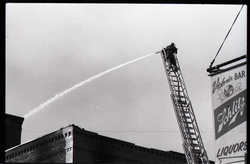 Fire on Main Street, Greenfield, Mass.: firefighter on ladder dousing flames (Greenfield, Mass.), linking to the digital object