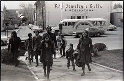 Group of commune members arriving, Free Spirit Press bus parked in background (Greenfield, Mass.), linking to the digital object