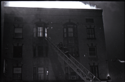 Fire on Main Street, Greenfield, Mass.: firefighters climbing ladder to burning building (Greenfield, Mass.), linking to the digital object