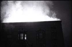 Fire on Main Street, Greenfield, Mass.: firefighter on ladder, with smoke and flames rising from burning building (Greenfield, Mass.), linking to the digital object