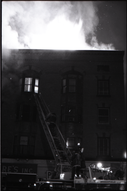 Fire on Main Street, Greenfield, Mass.: fire engine with ladder extended to burning building (Greenfield, Mass.), linking to the digital object