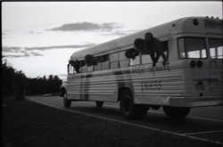 Free Spirit Press crew hanging out the windows of their bus (blurry) (Greenfield, Mass.), linking to the digital object