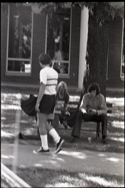 Young couple seated on park bench, reading copy of Free Spirit Press magazine (blurry) (Springfield, Mass.), linking to the digital object