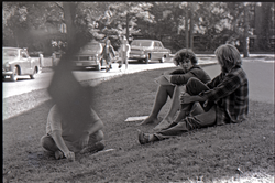 Young men seated on the grass next to copies of Free Spirit Press magazine (Springfield, Mass.), linking to the digital object