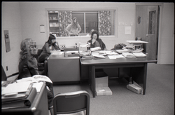 Unidentified person, Darlene Cobleigh, Bruce Geisler (behind glass), and Mike Scanlon (l. to r.) in office (Bennington, Vt.), linking to the digital object